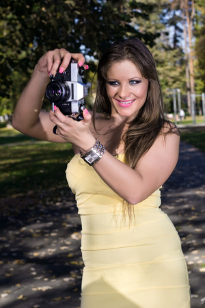 Beautiful young woman in a yellow dress photographed at the park Stock Photo