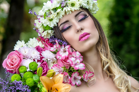 Beautiful woman in a flower wreath a in summer at sunset. Stock Photo