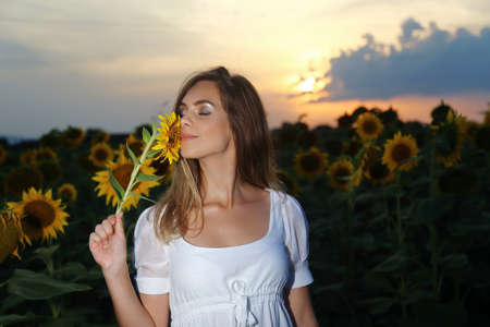 Happy carefree summer woman in sunflower field in spring