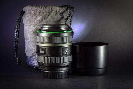 Professional DSLR lens on black background, Single optical lens on dark surface
