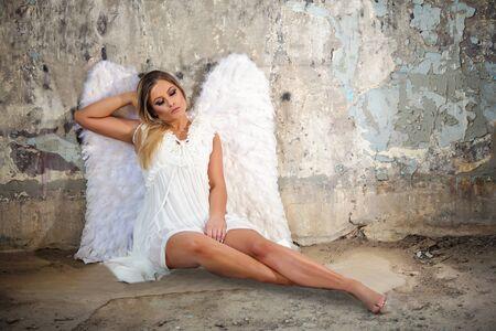 Sensual beautiful blonde with white wings and short dress Standard-Bild