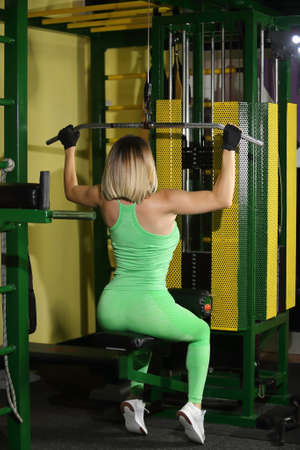 Blonde woman working at the lat pulldown machine in the gym