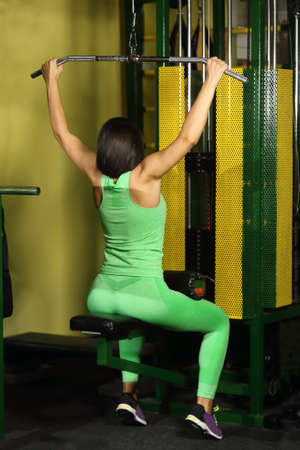 Brunette woman working at the lat pulldown machine in the gym