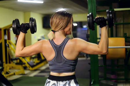 Blonde fitness woman is doing biceps dumbbells with both hands in the gym 免版税图像