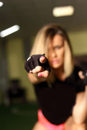 Fitness blonde woman posing in gym after workout sweaty