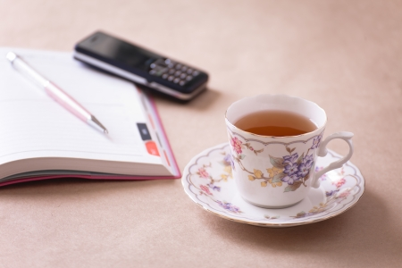 note pad and pen: tea, cellphone , notepad , pen on work table , teatime