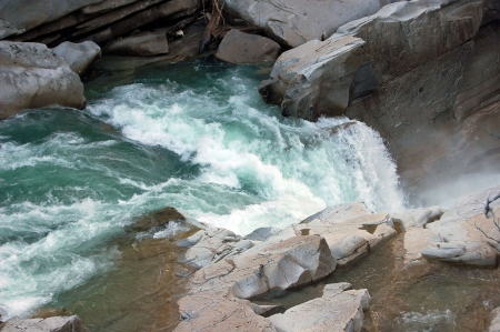 Skykomish raging river near Gold Bar Washington is a stunning photo of rushing water amidst rocks and an area of a small waterfall.
