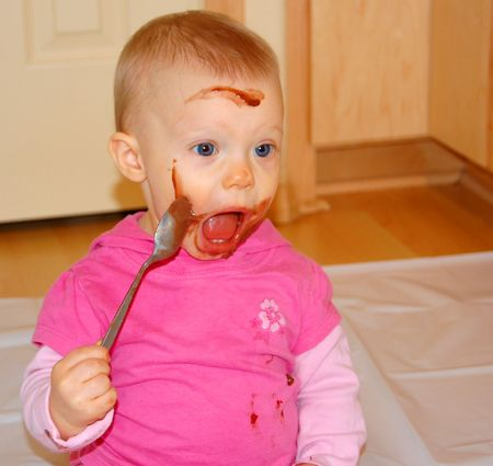 mess: Toddler misses her mouth while feeding herself chocolate pudding.  Very funny.