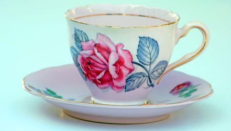Rosa pallido con disegni floreali antiche tazza di tè e piattino è un unico e raro vetro, contro uno sfondo bianco. Ha anche vernice oro intorno al cerchio. Archivio Fotografico - 4350061