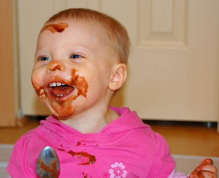 Baby with a very messy chocolate pudding on her face, laughing and having a great time. photo