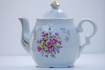 gold top: This white antique teapot has been in a family for several generations.  It has a hand painted floral design and a gold top and is set against a white background.  Truly unique piece. Stock Photo