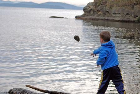 Ni�o llevaba una camisa azul est� lanzando una gran roca en el mar, con monta�as en el fondo, para una divertida acci�n de tiro chicos est�n chicos.