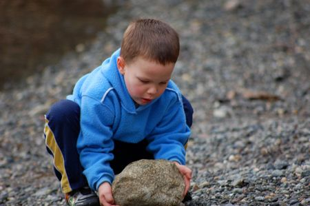 Little boy is squatting to pick up a large rock and focusing very much on this big task.