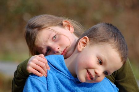 Grumpy sad big sister is holding onto smiling and content little brother in this cute sibling photo.