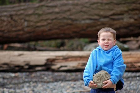 Little boy is picking up a big rock and has one eye closed because of the strength and concentration needed to do this task.