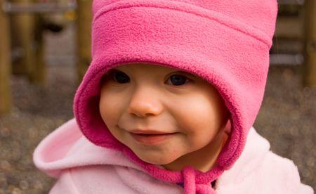 かわいい 1 歳の幼児の白人の子供は屋外で穏やかな笑顔でホットのピンクの帽子です。