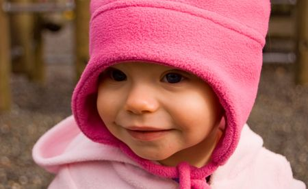 pink hat: A cute 1 year old toddler Caucasian child is outdoors in a hot pink hat with a gentle smile.
