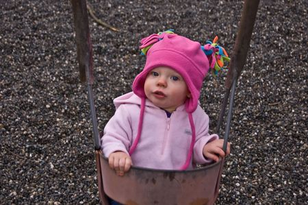 sure: Baby is in an outdoor swing for the first time and not quite sure what she thinks and feels about the experience.  Reserved expression.