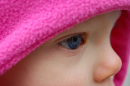 pink hat: Very closeup shot from a side view of a Caucasian babys blue eye, framed by a bright pink hat. Stock Photo