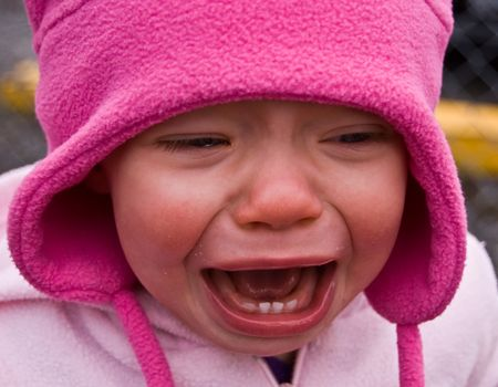 Baby girl is crying and very upset in this photo while wearing pink shirt & hat.