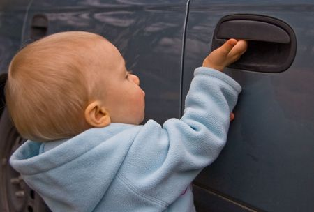 This small Caucasian child is trying to open a blue car door. photo
