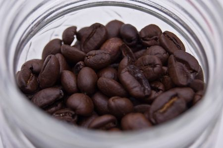 Closeup photo of fresh coffee beans in a glass jar against a white background.