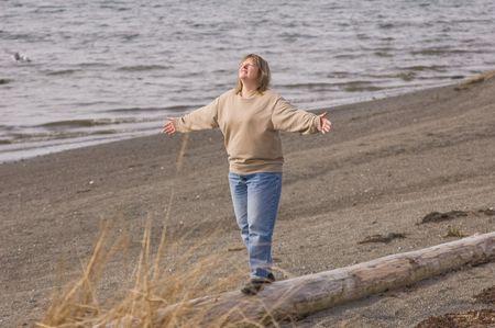 agradecimiento: Este medio de 40 a�os de edad mujer rubia es la celebraci�n de la vida en un momento en la playa caminando sobre un tronco. Hay una expresi�n de gratitud y de ser agradecidos.