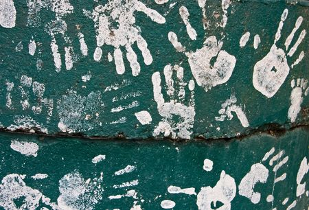 handprints: This is a collection of kids handprints in white paint, set against a green cement background.