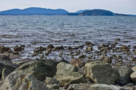 padilla: This photo is a seascape shot of the view at Padilla Bay Washington overlooking Hat Island off to the distance.  Beautiful ocean scene with rocks in the foreground and lots of muted blues.