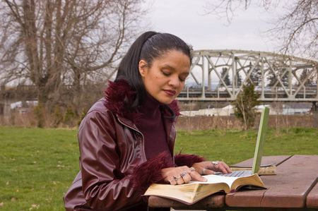 jamaican adult: Young professional woman is studying in the park with a laptop computer and book.  Model is in her late 20s and is multi ethnic of Jamacian, Irish & Native American.