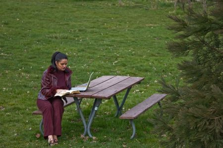 jamaican adult: Young woman multi ethnic is studying in a park at a picnic bench with a book and her laptop.