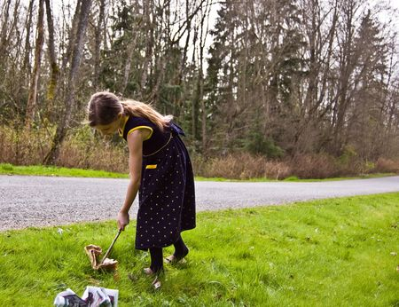 8 year old Caucasian child is picking up litter on the side of the road with a stick.  She's trying to practice good ecology at a young age.  She has long hair and is wearing a navy blue flowered dress.