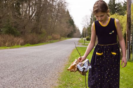 8 year old Caucasian girl is doing her share by cleaning up litter and garbage on a roadside to help the environment.  Shes wearing a navy blue flowered dress. photo