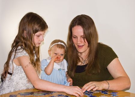This brunette young mom is doing a puzzle with 2 young girls.  The baby is rubbing her nose as shes getting sleepy.  Family bonding time while learning too.