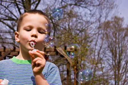 This young 4 year old boy is having a great time blowing bubbles outdoors. Stock Photo - 4709648