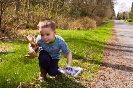 A young 4 year old Caucasian boy is picking up garbage on the side of the road to do his share for helping ecology and environmental issues. Stock Photo - 4709652