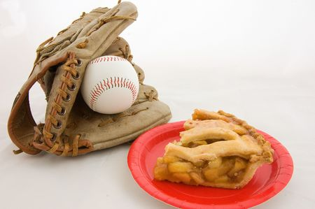 This is a closeup shot representing all American favorites baseball and apple pie.  Features a baseball mit, ball and a slice of fresh apple pie on a red plate, isolated on a white background. 版權商用圖片