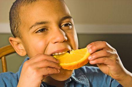 bi racial: This good looking bi-racial boy is enjoying a healthy snack of an orange slice.