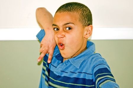 bi racial: This cute biracial 9 year old boy is doing a martial arts, kung fu type move in a humorous way.  This photo really shows off his fun personality. Stock Photo