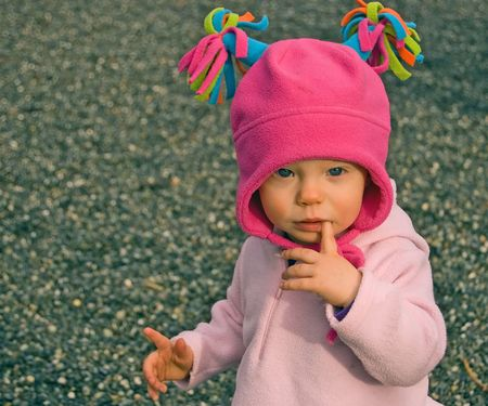pink hat: Little toddler girl is wearing a pink hat with tassels and has her finger in mouth while playing outdoors. Stock Photo