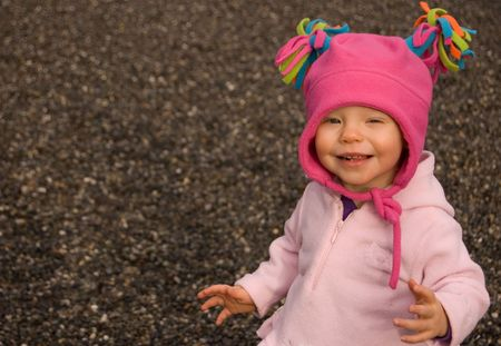 pink hat: Toddler girl wearing a bright pink hat with tassels is squinting while smiling.  Set against a backdrop of sand.