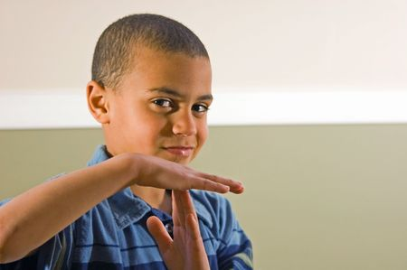 This nice looking 9 year old bi racial boy is signaling with his hands time out.