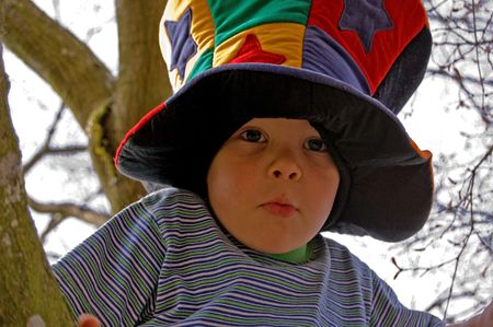 This wacky photo is a little boy climbing a tree in a wacky colorful mad hatter type hat. photo