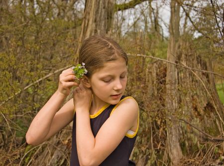 old photo: This is a sweet photo of a cute 8 year old Caucasian girl putting small blue flowers into her hair. Stock Photo