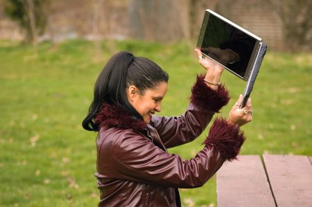 This young, multi ethnic professional woman is working at the park with her laptop and is so frustrated, she's about to throw it. photo