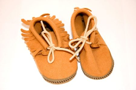 moccasins: This photo features a closeup pair of baby moccasin leather shoes with bow ties.