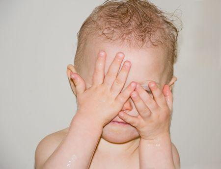 Linda foto de un beb� de raza cauc�sica vistazo a boo jugando en el ba�o, cubriendo sus ojos con las manos.