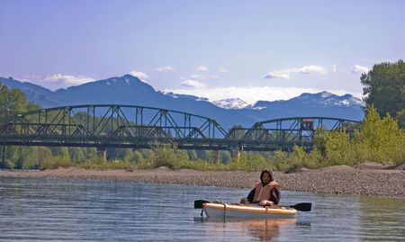 This young man is in a canoe on a beautiful river in the mountains with a bridge in the background. Stock Photo - 4840151