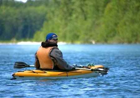 Young adult man is enjoying a leisure water sport of canoeing in a beautiful mountain river.