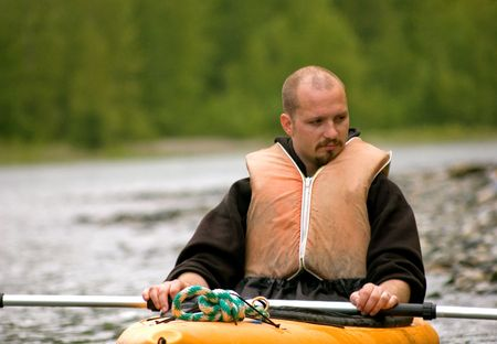 This young adult Caucasian guy is taking a break from kayaking and is deep in thought. Stock Photo - 4840149